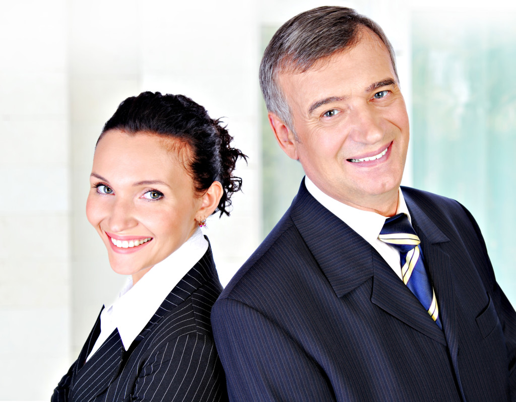 Portrait of a businessman and businesswoman leadership team smiling.